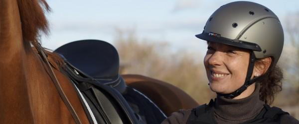 Eine Frau mit Reiterhelm und Reiterweste steht neben einem Pferd.